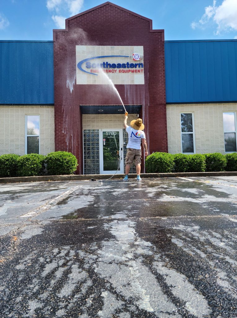 team member power washing a commercial building